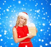 christmas, winter, happiness, holidays and people concept- smiling woman in santa helper hat with gi