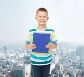 education, childhood and school concept - smiling little student boy with blue book over city backgr
