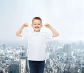 advertising, people and childhood concept - smiling little boy in white blank t-shirt with raised ha
