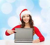 christmas, holidays, technology, advertisement and people concept - smiling woman in santa helper ha