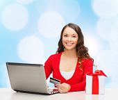 christmas, holidays, technology and shopping concept - smiling woman with credit card, gift box and