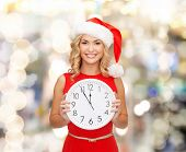 christmas, winter, holidays, time and people concept - smiling woman in santa helper hat and red dress with clock over lights background