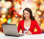 christmas, holidays, technology and shopping concept - smiling woman with credit card and laptop com