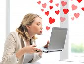 virtual relationships, online dating and social networking concept - woman sending kisses with lapto