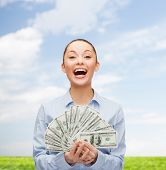 business, holidays and people concept - laughing businesswoman with dollar cash money