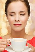 leisure, happiness and drink concept - smiling woman in red dress with closed eyes holding cup of co
