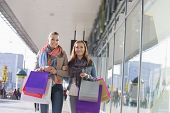 Happy female friends with shopping bags walking on sidewalk
