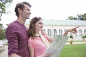 Woman with map showing something to man against building