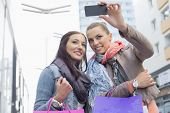 Female friends with shopping bags taking photos through mobile phone
