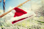vacation, christmas and holiday concept - picture of hammock with santa helper hat