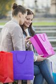 Woman with friend looking into shopping bag outdoors
