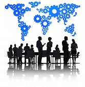 Business People Discussing Around The Conference Table And A Blue Cartography Of The World Made Of G
