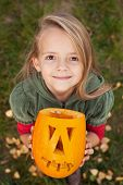 Autumn portrait with a Halloween pumpkin jack-o-lantern - little girl looking up