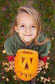Autumn portrait with a Halloween pumpkin jack-o-lantern - little girl looking up