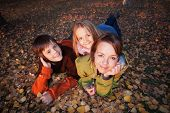 Family autumn portrait - laying on the ground among yellow leaves