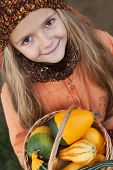 Little girl with a basketful of pumpkins - autumn portrait