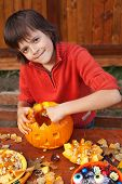 Boy preparing for Halloween - carving a pumpkin jack-o-lantern outdoors