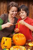 Boy and his mother having fun carving a jack-o-lantern for Halloween