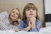 Thoughtful boy with mother in bed