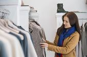 Woman selecting sweater in store