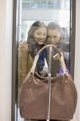 Happy female friends looking at purse through display window