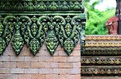 Brick Wall With Beautiful Green And Black Fretwork On Top Of It And Stairs With Elefant Statues At T