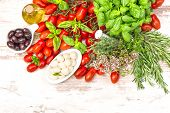 Tomatoes, Basil Leaves, Mozzarella And Olive Oil. Food Background