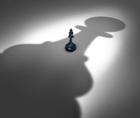 foto of change management  - Management change and new leadership concept or changing a manager in the future as a symbol with a chess king facing a giant cast shadow of a pawn as an icon of upcoming business power - JPG