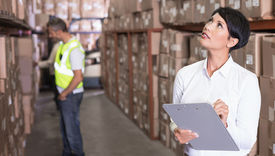 stock photo of warehouse  - Pretty warehouse manager checking inventory in a large warehouse - JPG