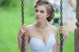 stock photo of runaway  - Beautiful bride sitting on the swings in the Park - JPG