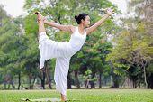 stock photo of natarajasana  - Beautiful woman practicing yoga in the park - JPG