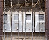 stock photo of electricity meter  - Group of old dirty electricity meters behind a metal grill - JPG