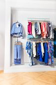 Many children clothes in store on white wall