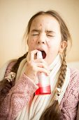 Young Girl With Flu Using Throat Spray