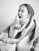 Monochorme Portrait Of Little Girl In Bed Using Throat Spray
