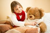 Girl Lying In Bed And Measuring Teddy Bears Temperature With Thermometer