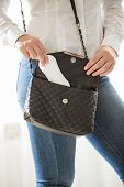 picture of menses  - Closeup photo of young stylish woman putting hygiene pad in handbag - JPG