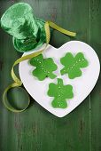 picture of shamrock  - Happy St Patricks Day shamrock shape green fondant cookies on white heart shape plate on vintage style green wood table.