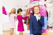One boy with shopping bag and girls choose clothes