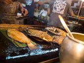 Man Grills Fish In Asian Restaurant