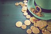 foto of pot gold  - Happy St Patricks Day leprechaun hat with gold chocolate coins on vintage style green wood background with retro vintage style filters.