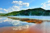 Red Steamy Surface And Reflection Of The Clouds In Midway Geyser Basin In Yellowstone National Park,