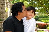 pic of average looking  - A Hispanic father gives a kiss to he young son - JPG