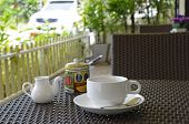 White coffee set on the table at an outdoor cafe on a summer day