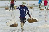 Man carries salt at the salt farm in Huahin, Thailand.