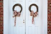 picture of red siding  - Christmas wreaths hanging on doors outside with red ribbon bows - JPG