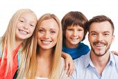 pic of family bonding  - Happy family of four bonding to each other and smiling while standing against white background - JPG