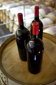 picture of bordeaux  - Three bottles of Bordeaux red wine on a barrel - JPG