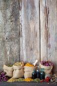Healing Herbs In Hessian Bags On Old Wooden Background, Herbal Medicine.