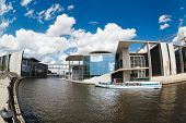 Two Tourists Ships Floats On The River Spree Next To A Modern Buildings Of Bundestag And Marie-luder
